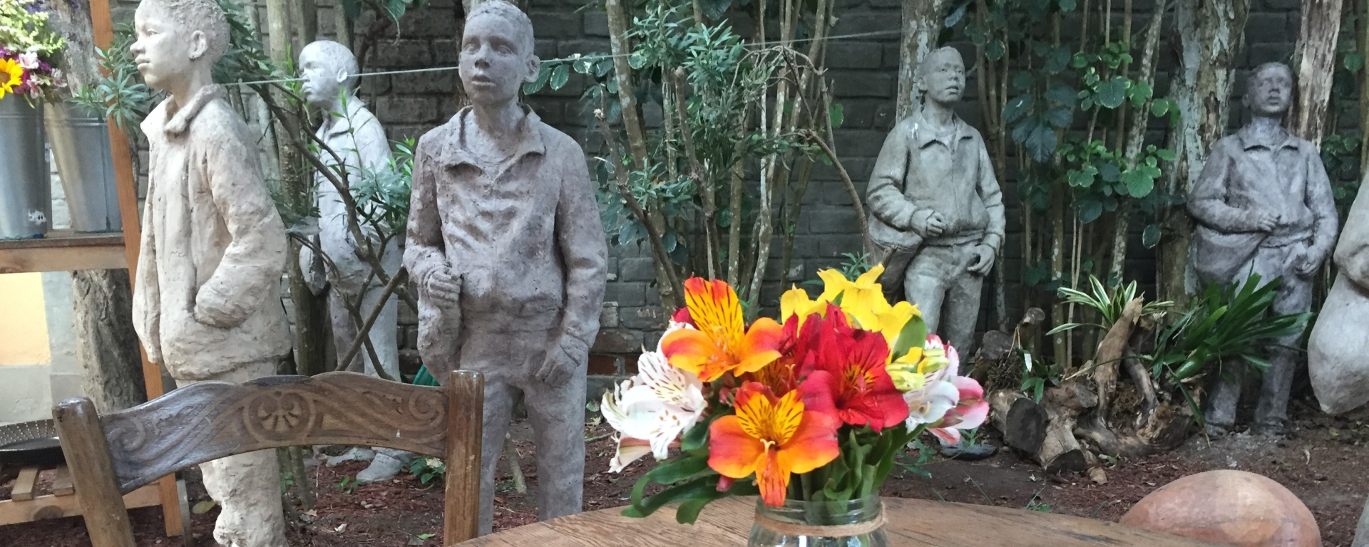 Wooden table with flowers in garden, Barranco, Lima, Peru with statues of children in the background